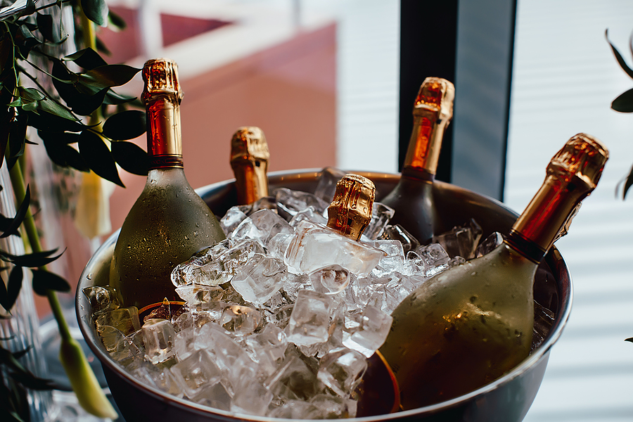 Five wine bottles chill in ice bucket on a buffet table