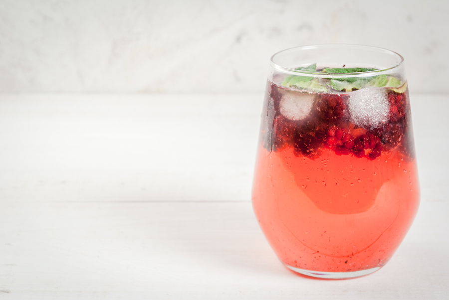 Summer refreshing drink. Gin tonic with mint leaves and blackberries. On a white wooden table.